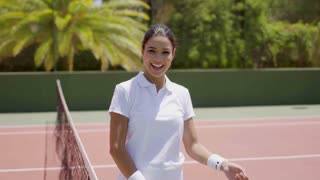 Pretty female tennis player with racket and ball
