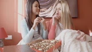 Pretty Girls Eating Chocolates Inside Bedroom