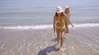 Pretty girls in bikinis paddling in the sea