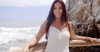 Pretty Lady Leaning her Back Against Beach Railing