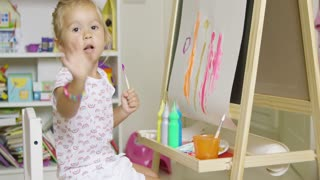 Pretty little girl artist sitting at an easel painting a colorful abstract picture with watercolors pausing to look earnestly at the camera
