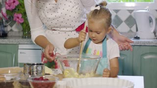 Pretty little girl helping out in the kitchen learning to bake standing with her mother mixing ingredients in a glass mixing bowl with a spoon
