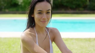 Pretty sincere young woman in a summer garden sitting in her bikini on the grass with a cool inviting pool in the background smiling at the camera.