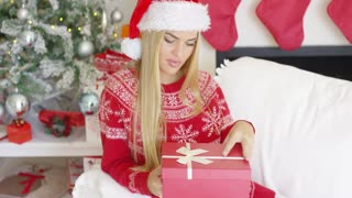 Pretty smiling blondie looking at her boxed christmas gift while sitting on sofa in her perfectly decorated home.