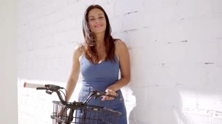 Pretty smiling woman with a bicycle