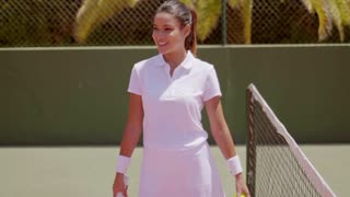 Pretty tennis player tosses ball and swings racket
