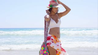Pretty trendy young woman posing on a windy beach in a colorful sarong on a hot summer day holding her straw sunhat with her hand
