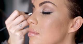 Pretty woman applying eye liner on her eyelid