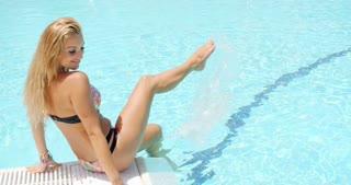 Pretty Woman in Bikini Sitting on the Poolside