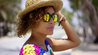 Pretty woman in sunglasses and hat outside