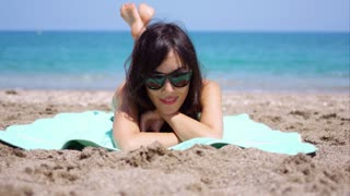 Pretty woman in sunglasses sunbathing on a beach lying on a towel facing the camera on the golden sand with the sea behind her