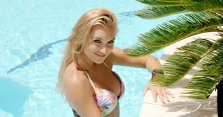 Pretty woman in the pool holding palm leaves