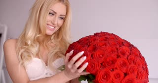 Pretty Woman in White Bra Touching a Rose Bouquet