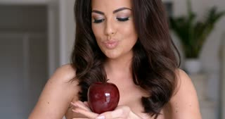 Pretty Woman Looking at Red Apple on her Hand