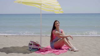Pretty woman on blanket under beach umbrella
