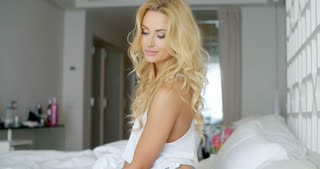 Pretty Woman Sitting on her Bed with Hand on Face