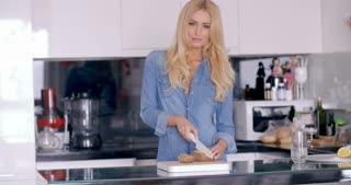 Pretty Woman Slicing a Bread at the Kitchen