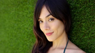 Pretty woman wearing top with green strap piles hair over one shoulder and smiles at camera while laying in grass