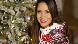 Pretty woman with a lovely smile celebrating Christmas standing in front of a decorated tree in her living room close up portrait
