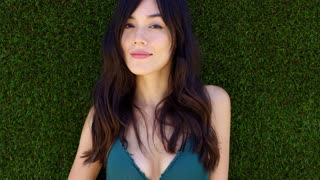 Pretty woman with long brown hair lays in grass while smiling up at the camera and wears green bikini