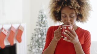 Pretty young African woman enjoying coffee