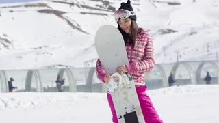 Pretty young asian woman on snowy slope holding her snowboard. She smiling to the camera. Wearing pink ski outfit and goggles. Enjoys winter holidays.