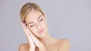 Pretty young blond woman making a sleep gesture resting her head on her hands with her eyes closed and a serene expression