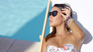 Pretty young brunette woman sunbathing poolside in a deck chair in her swimsuit and sunglasses close up view