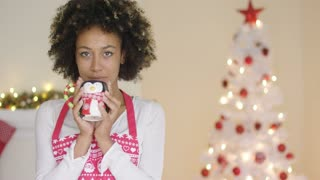 Pretty young housewife relaxing at Christmas standing in her festive apron enjoying a mug of coffee in front of the tree