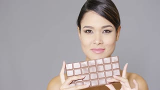 Pretty young woman biting into a bar of chocolate with a smile of anticipation isolated on grey