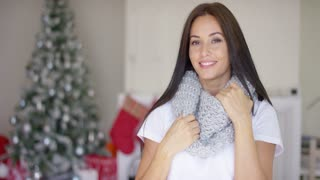 Pretty young woman celebrating the Christmas season at home in a stylish warm winter scarf standing near the decorated tree smiling at the camera