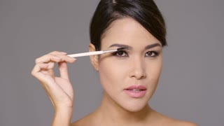 Pretty young woman contouring her eyebrows with a cosmetics brush in a close up beauty portrait on grey
