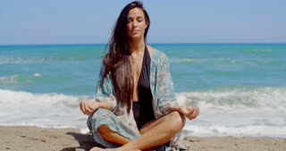Pretty Young Woman Doing Yoga at the Beach