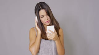 Pretty young woman enjoying her music as she listens to her library on her mobile phone on a set of stereo headphones