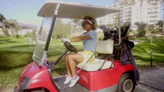 Pretty young woman golfer in a red golf cart