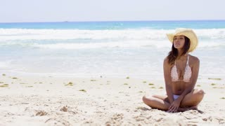 Pretty young woman in a bikini relaxing on a tropical beach sitting cross-legged in the sand with her back to the ocean looking at the camera.