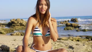 Pretty young woman in a bikini sitting cross-legged on a rocky beach with her hand to hair looking at the camera with a thoughtful expression.