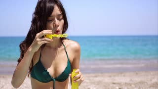 Pretty young woman in a bikini standing blowing iridescent party bubbles on a beach with a calm ocean behind her