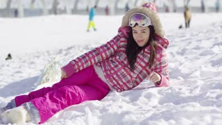 Pretty young woman in pink snowsuit lying on snow with ski goggles