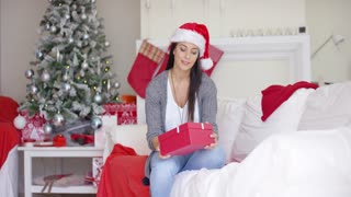 Pretty young woman opening a Christmas gift with a joyful smile as she relaxes on a sofa in her living room in front of the Xmas tree.