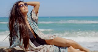 Pretty Young Woman Relaxing at the Beach Sand