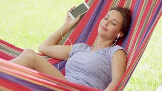 Pretty young woman relaxing in a colorful striped hammock in the garden listening to music on her mobile phone or storage device