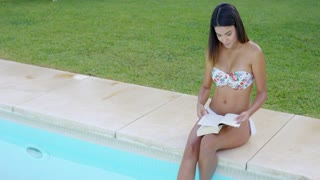 Pretty young woman relaxing with a book sitting on the edge of a swimming pool with her feet in the water