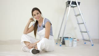 Pretty young woman renovating her home sitting on the floor in front of a stepladder and paint grinning at the camera