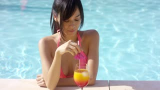 Pretty young woman sipping a tropical cocktail as she cools off in a refreshing swimming pool on summer vacation
