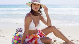 Pretty young woman sitting on the beach sand at the edge of the ocean in her bikini and sarong holding her sunhat in the sea breeze.