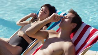 Pretty young woman smiling and relaxing with her boyfriend in a deck chair alongside a swimming pool as they enjoy their summer vacation