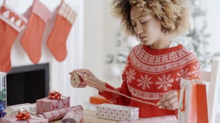 Pretty young woman wrapping Xmas presents
