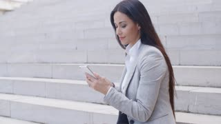 Pretty young worker sitting on steps with phone
