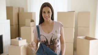 Proud young woman holding up a set of house keys as she stands in her new living room surrounded by packed brown cardboard boxes
